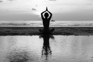Silhouette young woman practicing yoga on the beach. Black-and-white contrast photo.