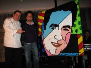 celebrating-with-a-bamromero-britto-presents-emeril-lagasse-with-a-painting-during-his-five-year-anniversary-celebration-2